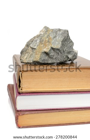 Books lay pile on top of them and the stone - stock photo