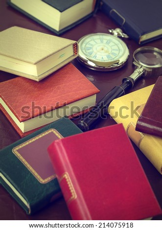 Books, magnifying glass, glasses and watch on a leather background.Vintage effect. - stock photo