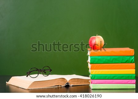 Books near empty green chalkboard. Sample for text