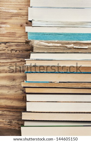 Books next to the wooden wall - stock photo