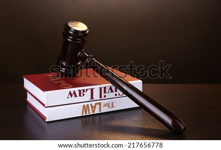 Books of Law and hammer on table on brown background