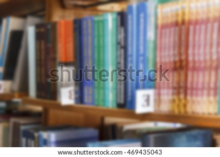 books on a shelf in the library, reading, and science education, stack of books piled volume hardcover blurred