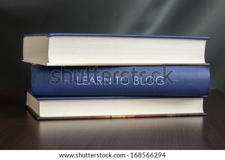 "Books on a table and one with "" Learn to blog "" cover. Book concept. - stock photo"
