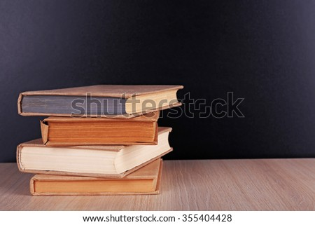 Books on a table on blackboard background