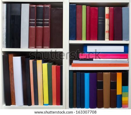 Books on a white shelf - stock photo