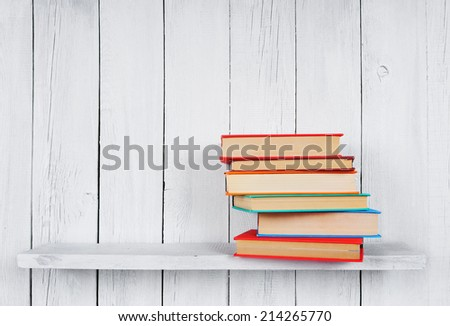 Books on a wooden shelf. On a wooden, white background.