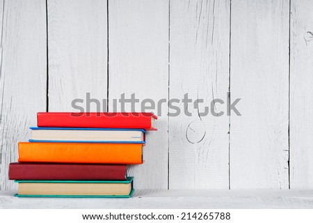 Books on a wooden shelf. On a wooden, white background. - stock photo