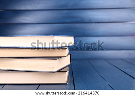 Books on dark blue wooden background