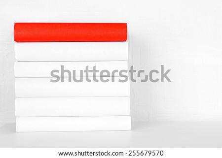 Books on shelf on wall background - stock photo