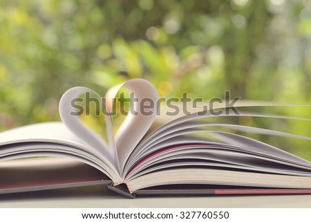 books on table in garden with top one opened and pages forming heart shape  - stock photo
