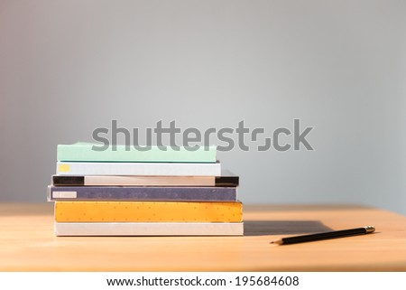 Books on the table. No labels, blank spine and pencil. - stock photo