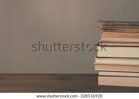 Books on wooden table and grunge background. Vintage background.
