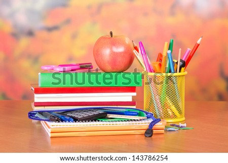 Books, pencils and handles in a support, a pencil-case, a scissors and apple, on a table