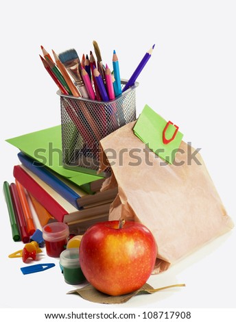 books, pencils, apple, package with a sandwich on a white background - stock photo