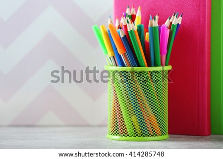 Books pens and markers in metal holder on colour background