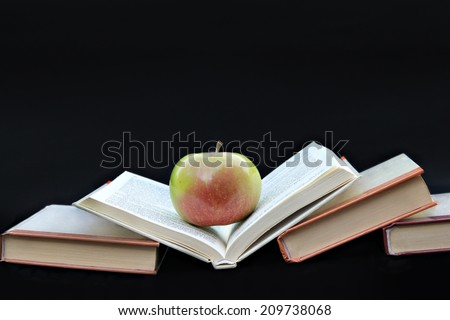 Books  Pile of books with apple on black background - stock photo