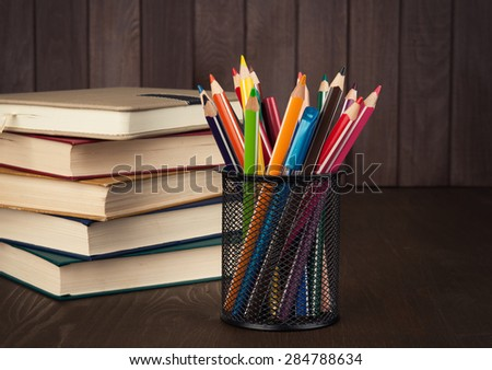 books stack and pencils on wooden desk. education supplies - stock photo