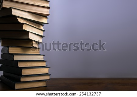 Books stacking. Back to school background. Purple wall.