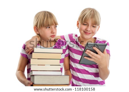 Books vs ebook reader - Two girls demonstrating the difference. One of them holding lots of books while another reading an ebook reader and smiling. - stock photo