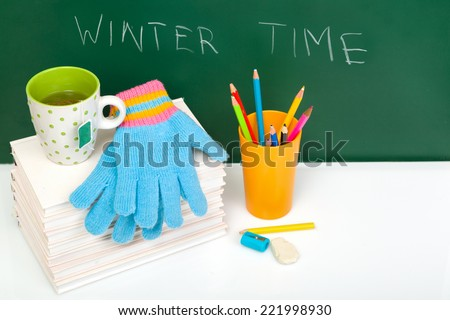 Books, winter gloves, cup of tea and used pens on white desk against green chalkboard. Winter time. Winter break. View from above.