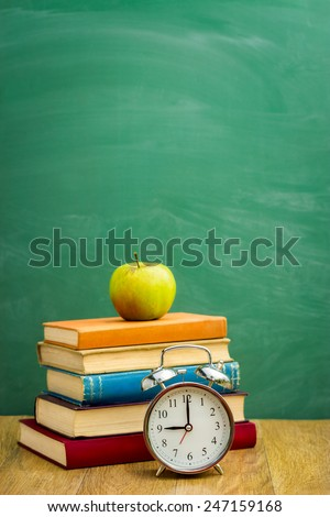 Books with alarm clock on the background of the school board - stock photo