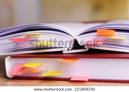 Books with bookmarks on table on bright background - stock photo