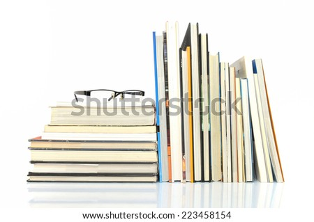 Books with glasses on white background - stock photo