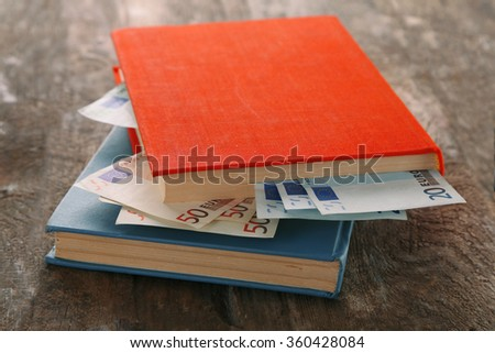 Books with nested euro banknotes on wooden table. Stash of money - stock photo