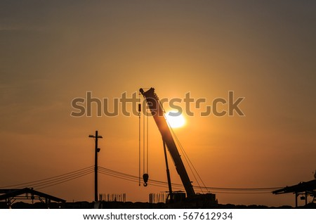 Boom of mobile crane silhouette with sunrise background
