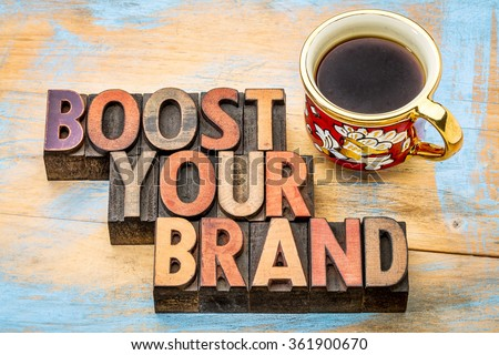 boost your brand - isolated text in vintage letterpress wood type, stained by color inks, with a cup of coffee - stock photo
