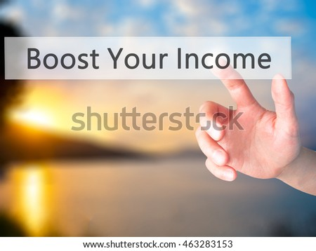 Boost Your Income - Hand pressing a button on blurred background concept . Business, technology, internet concept. Stock Photo