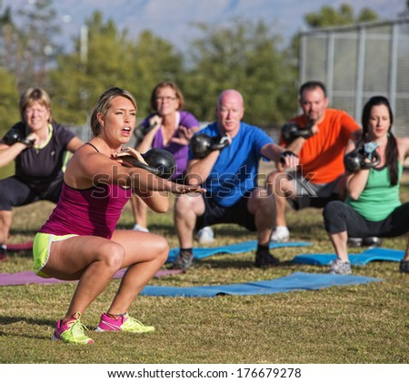 Boot camp fitness trainer yelling during squat exercises - stock photo