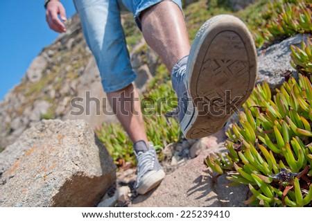 Boot closeup on mountain rocks in Cabo da Roca, Portugal - stock photo