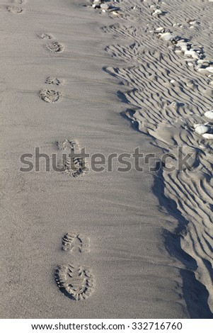 Boot track footprints on a sandy river beach. - stock photo