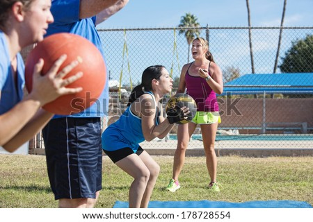 Bootcamp fitness instructor training adults with medicine ball - stock photo