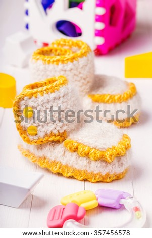 Booties for babies handmade surrounded by toys - stock photo