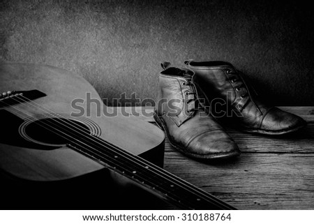Boots and guitar on wooden table over grunge background, black and white