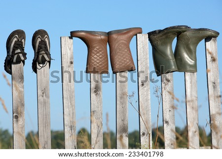 Boots and shoes are dried on the fence after rain, Russia.