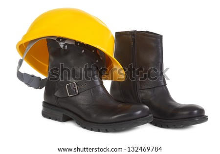 Boots and yellow hard hat over white background, small natural shadow under boots - stock photo