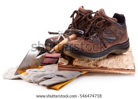 Boots, gloves, goggles and trowel with tiles