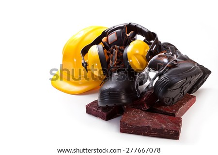 Boots, headphones against noise, yellow hard hat and stone cladding on a white background - stock photo