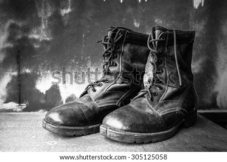 Boots shoe on old wooden table. - stock photo