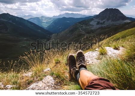 Boots traveler in the mountains. Legs and mountain views