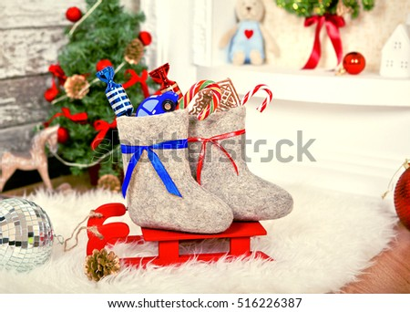 Boots with Christmas gifts on red sled