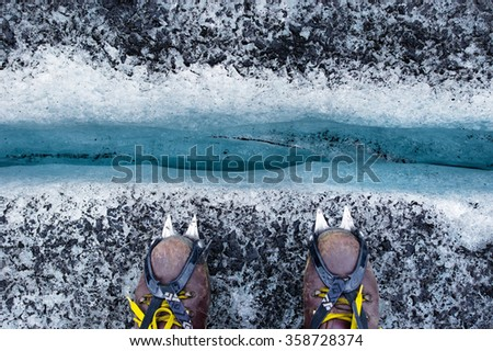 Boots with crampons and deep glacier cleft - stock photo