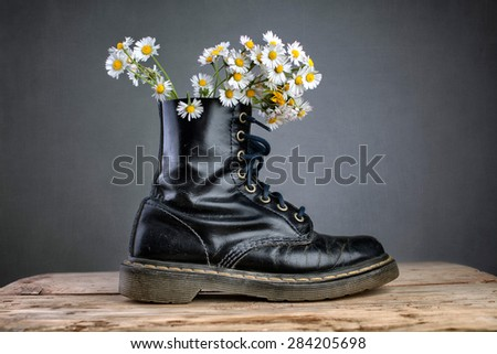 Boots with Daisy Flowers - stock photo
