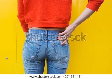 Booty young slim girl in jeans and a red blouse on a yellow background, and the phone in your pocket - stock photo