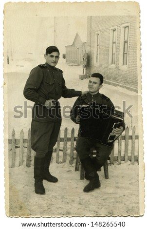 BOR, RUSSIA, USSR - CIRCA May 26, 1972: Vintage photo shows two soldier with harmonica, Bor city, Russia, May 26, 1972 - stock photo