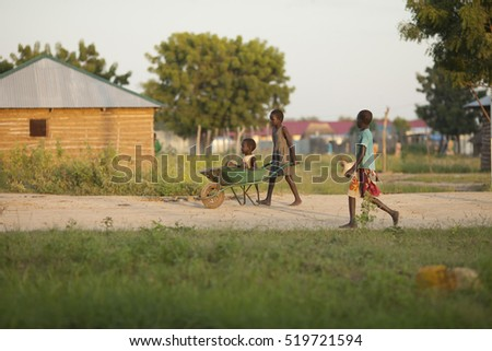 BOR, SOUTH SUDAN-OCTOBER 30, 2013: Unidentified children carry a small child in a wheel barrow in South Sudan
