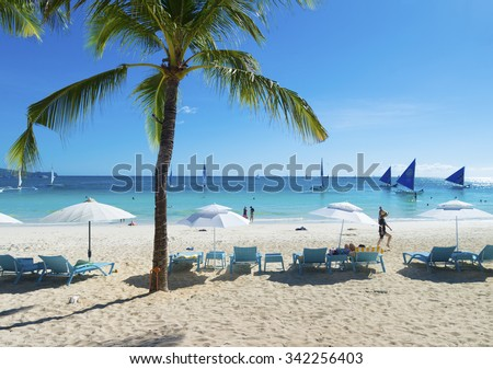 BORACAY, PHILIPPINES - MAY 5, 2015: Tourists on tropical beach. Boracay is one of the main tourist attractions in the philippines because of its white beaches